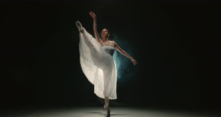 poddasze : 4K video footage beautiful woman ballerina in white tutu on black background, slow motion Wideo