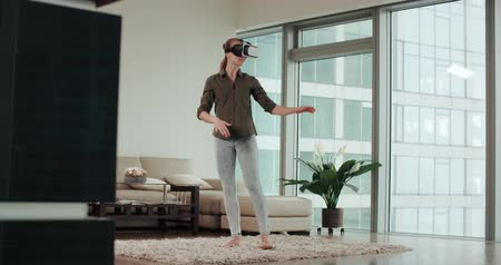 first person : woman in VR virtual reality glasses in a modern living room Stock Footage
