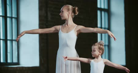 magánélet : adult ballerina teaching a little girl, classical ballet in the loft Studio