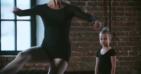 squatting : adult ballerina teacher coached a little girl in dance class