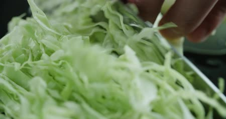 wok food : cabbage slicing in slow motion macro, the chef works in the kitchen
