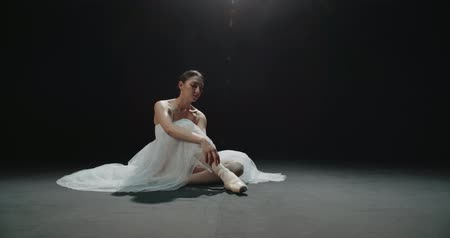 тапочка : ballerina putting on pointe before performance