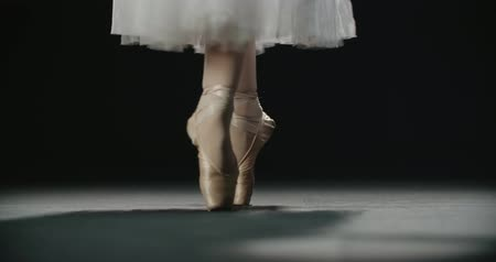 театральный : close-up footage, ballerinas feet in pointe shoes during performance of classical ballet elements