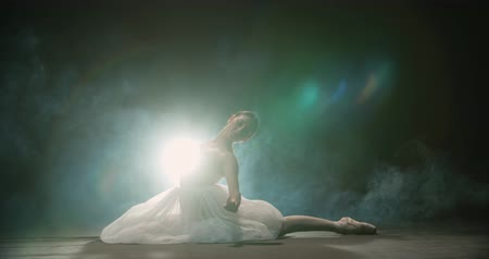 fabuloso : Ballerina performs elements of classical ballet, black background, smoke, slow motion Stock Footage