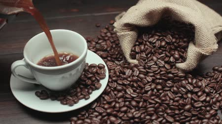 coffee press : pouring a Cup of hot coffee and roasted coffee beans on the table, slow motion