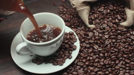 feijões : pouring a Cup of hot coffee and roasted coffee beans on the table, slow motion