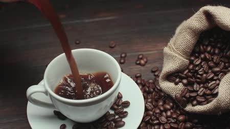 coffee press : pouring a Cup of hot coffee and roasted coffee beans on the table, slow motion, Dolly shot Stock Footage