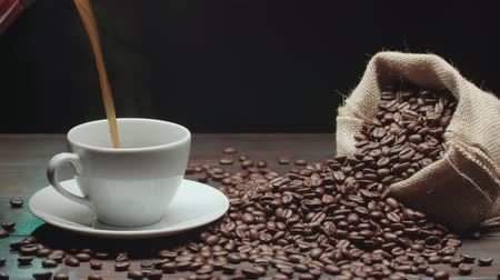kitchenware : pouring a Cup of hot coffee and roasted coffee beans on the table, slow motion