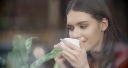 rüya gibi : Girl with a cup of coffee in a cafe, dreamily watching the street life of the city, outside view, close-up