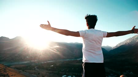 alcançando : young Asian male reaching to the top of the mountain area, standing on top of a mountain, hands raised, awareness of success, slow motion Vídeos