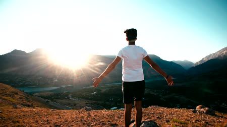 достигать : young Asian male reaching to the top of the mountain area, standing on top of the mountain, raised hands, slow motion