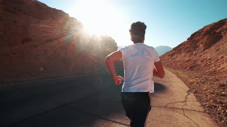 letecký : a young Asian man Jogging along the old mountain road, the pursuit of goals, the sun glare, slow motion
