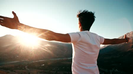 alcançando : young Asian male reaching to the top of the mountain area, standing on top of a mountain, hands raised, awareness of success, slow motion Stock Footage