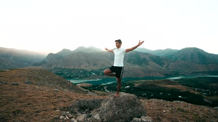 спокойный : young Asian man doing yoga in a mountain area, standing on top of a mountain, healthy life, sun glare, slow motion Стоковые видеозаписи
