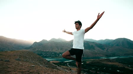рука : young Asian man doing yoga in a mountain area, standing on top of a mountain, healthy life, sun glare, slow motion Стоковые видеозаписи