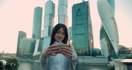 felhőkarcoló : beautiful successful business woman Asian model makes a selfie photo with skyscrapers in the background
