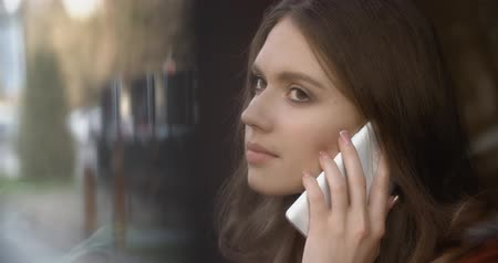 ahead : Beautiful woman talking on cellphone in cafe Stock Footage