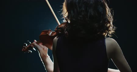 outstanding : a talented girl violinist performs at her first solo concert, stage light, dark background