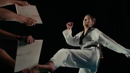 batalha : Asian beautiful girl fighter practicing to break the board with a kick of the feet, slow motion