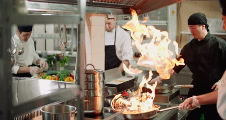 komerční : chef actively working in the kitchen of the restaurant with Asian cuisine, vegetables are roasted with fire,4K slow motion Dostupné videozáznamy