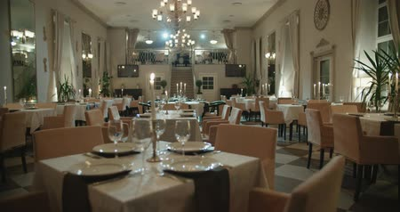 toalha de mesa : an empty restaurant hall, a table for two served candle light, ready to receive guests, dolly shot