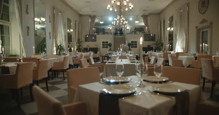 luxo : an empty restaurant hall, a table for two served candle light, ready to receive guests, dolly shot