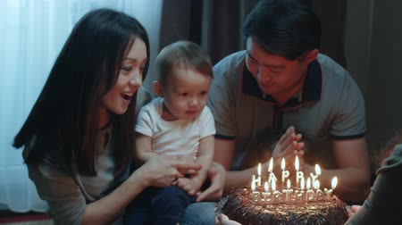 felicitação : Asian family with two children congratulates the baby son with the first year, the birthday cake with burning candles