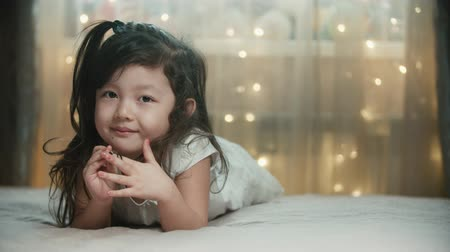 carelessness : little 5-6 years old cute asian girl having fun, smiling and dreaming in her room Stock Footage