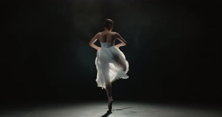 ustalık : 4K video footage beautiful woman ballerina in white tutu on black background, slow motion Stok Video