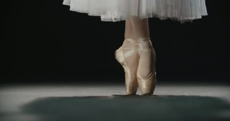 bird learning : close-up footage, ballerinas feet in pointe shoes during performance of classical ballet elements, slow motion Stock Footage