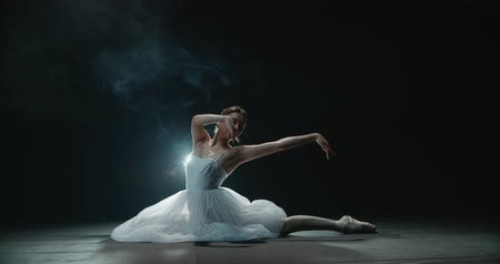 teljesít : Ballerina performs elements of classical ballet, black background, smoke, slow motion Stock mozgókép