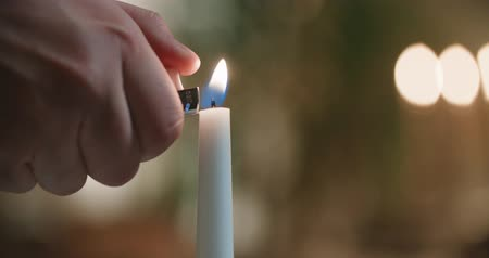 элита : close-up of a mans hand lighting a candle