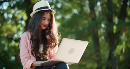 rejoice : girl in the park with a laptop, much expresses joy, the student learned about the successful passing of the exam