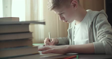 schoolkid : 4k,Teenage boy studying - doing his homework dolly shot