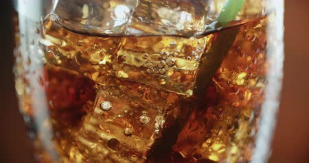 coque : Cola with ice. Extreme close-up, drink through a straw for a coke with ice cubes and bubbles in a big glass.
