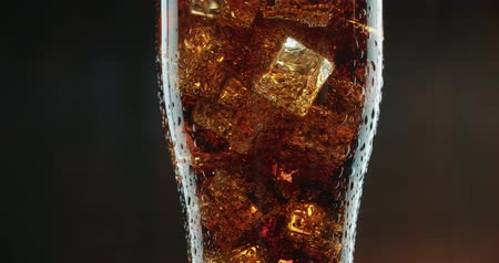 coque : Cola with ice. Extreme close up of Cola with Ice cubes and bubbles in the big rotating glass. Soda.4k stock video footage.