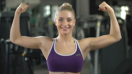 голова и плечи : portrait of a young beautiful sporty girl is smiling and looking at camera on the background of the gym Стоковые видеозаписи