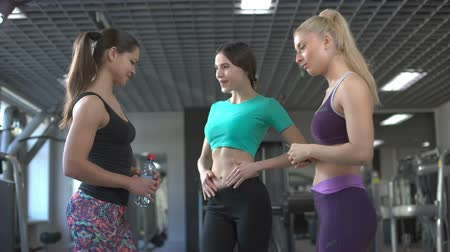 socializing : three women chat in the gym friendship successes to boast a thin waistline