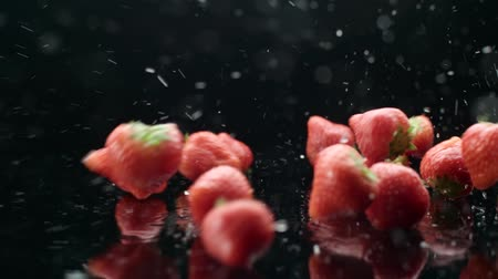 video reel : strawberry rain, juicy ripe berries fall from the water in slow motion, black background Stock Footage