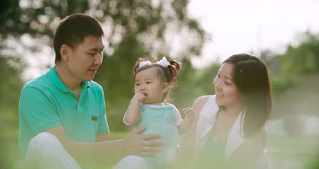 nenúfar : young Asian family with a year-old baby in a Park during a picnic, have fun, slow motion, close up