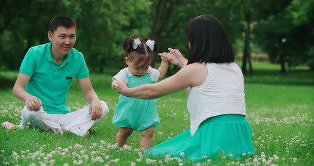 nenúfar : young Asian family with a year-old girl in the Park teach your child to do first steps, slow motion,