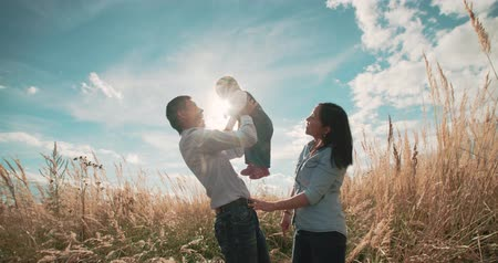 asian family : young Asian family in a field with a baby 1 year on hand, the concept of family happiness, beautiful sunlight, sunset, slow motion