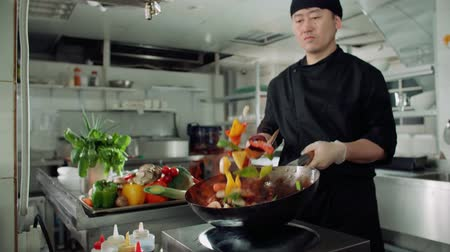 chef cooking : Asian chef works coloured mixed roasting vegetables in the wok with flame , kitchen Asian restaurant, slow motion