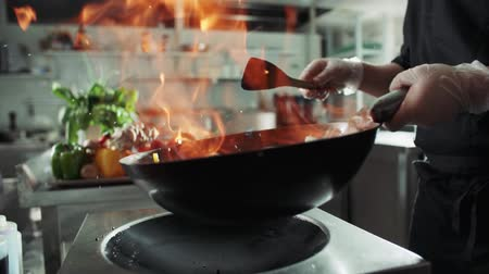 wok food : close-up of a chef working the wok with flames roasting mixed colorful vegetables tossing them , restaurant kitchen , slow motion
