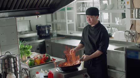 wok food : chef works mixed colored roasting vegetables in the wok-tossing and flames , kitchen Asian restaurant, slow motion