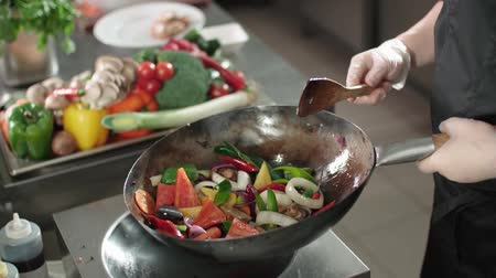 frigideira : close-up cook actively roasting mixed colorful vegetables wok-tossing in the kitchen of an Asian restaurant, slow motion