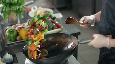 wok food : close-up cook actively roasting mixed colorful vegetables wok-tossing in the kitchen of an Asian restaurant, slow motion