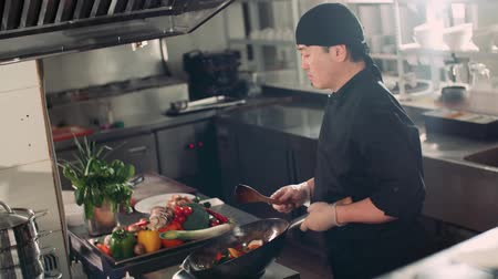 beyazlar : the cook is actively roasting mixed colorful vegetables wok-tossing in the kitchen of an Asian restaurant, slow motion Stok Video