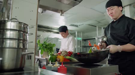 wok : male chef actively working in the kitchen of an Asian restaurant mixed colorful vegetables are roasted in a wok in slow motion Stock Footage