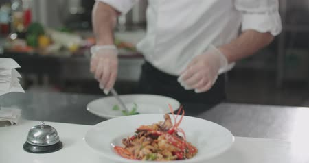 kazık : chef serves a dish of seafood on a plate adding the final ingredients